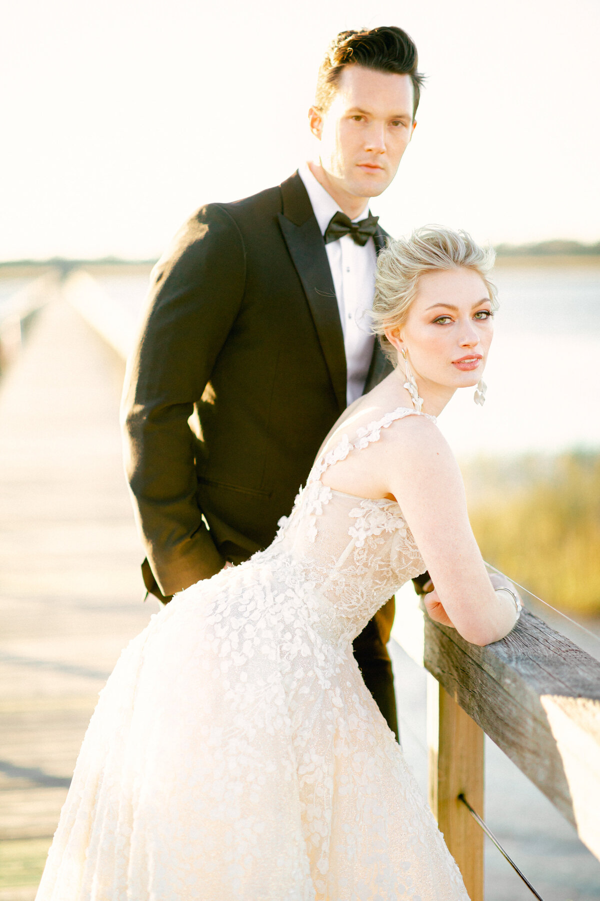 Bride and groom standing on wooden dock on river at Charleston Wedding