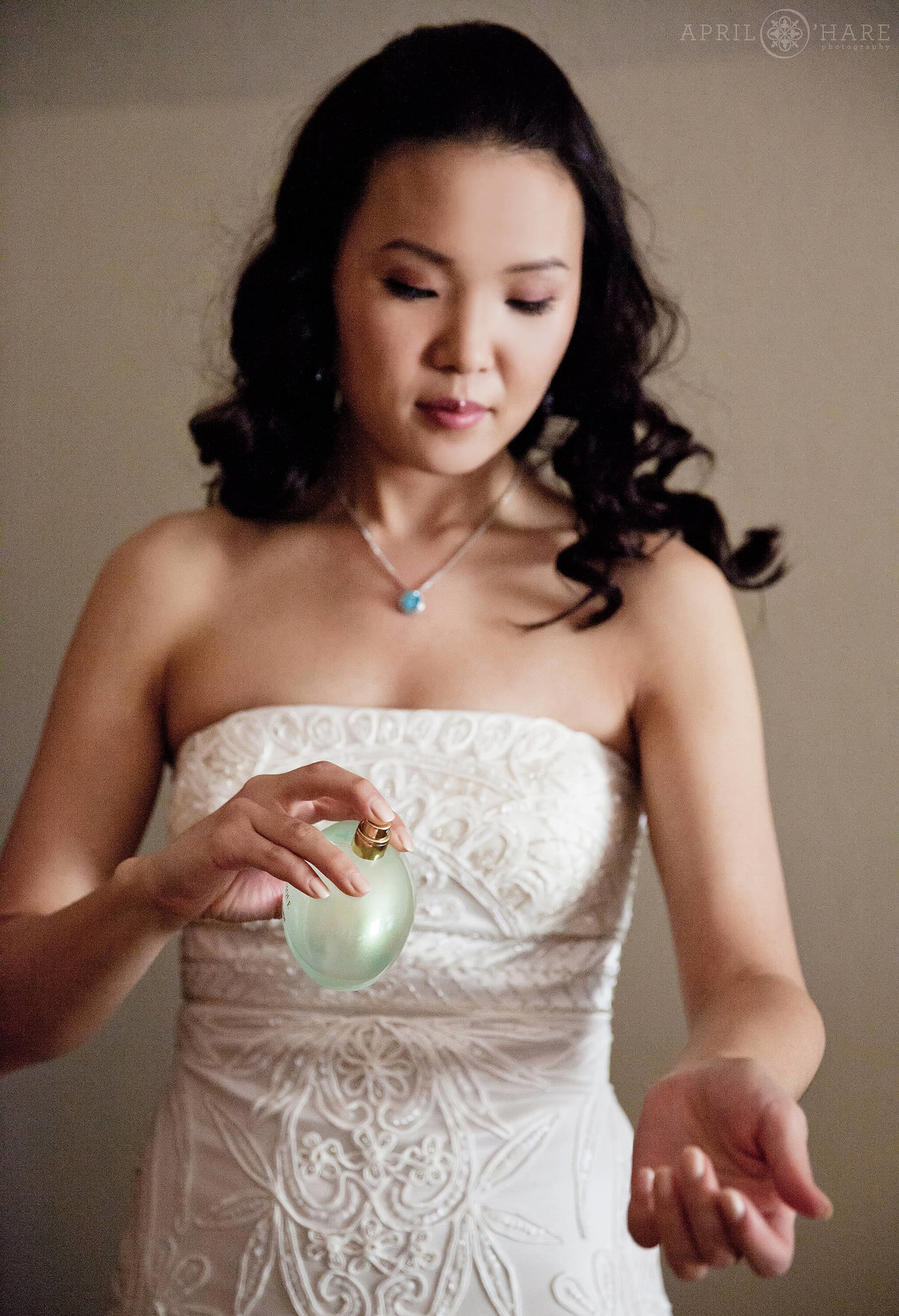 A pretty Asian bride squirts some perfume on the day of her Estes Park wedding at a VRBO house in Colorado
