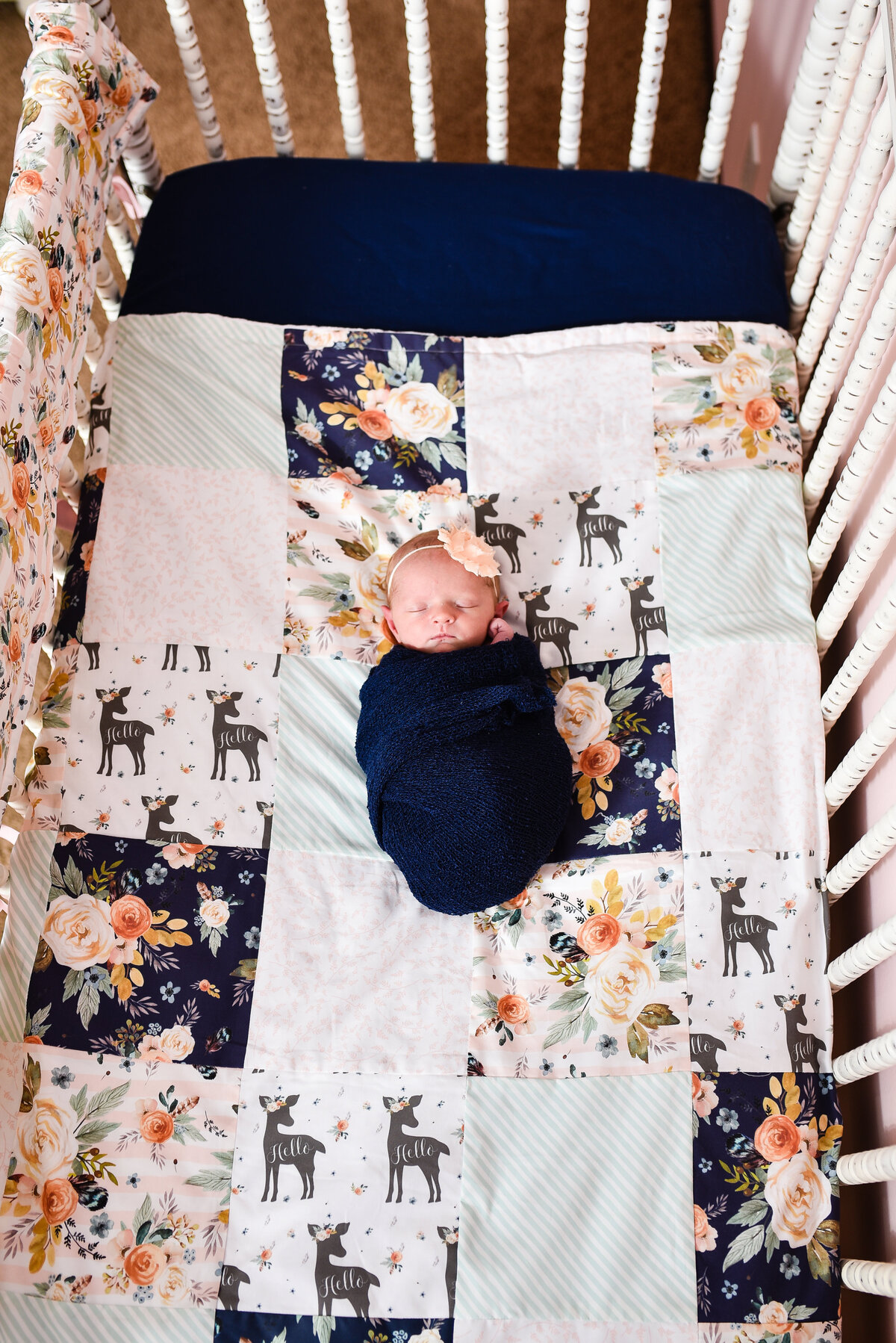 Beautiful  lifestyle newborn photography: Newborn girl wrapped in navy in her crib with cnavy and peach floral bedding