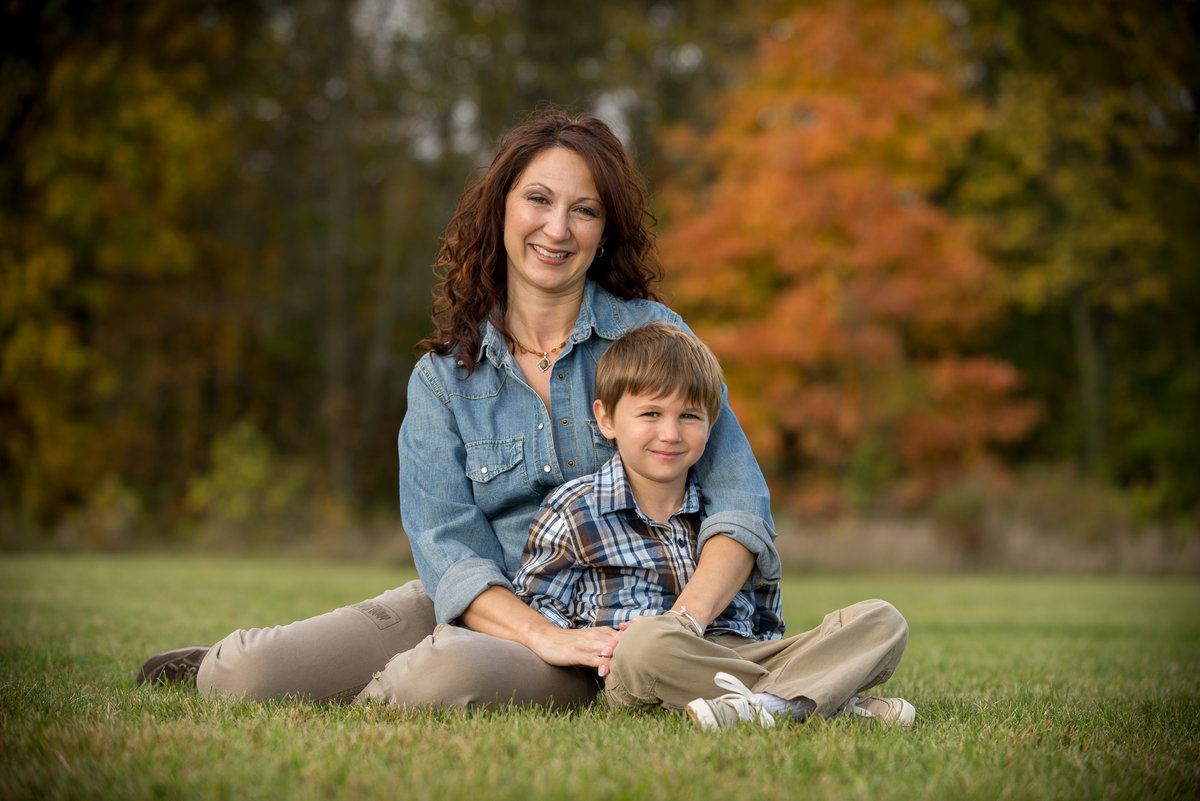Single mom and her son sit in a field for a autumn family portrait