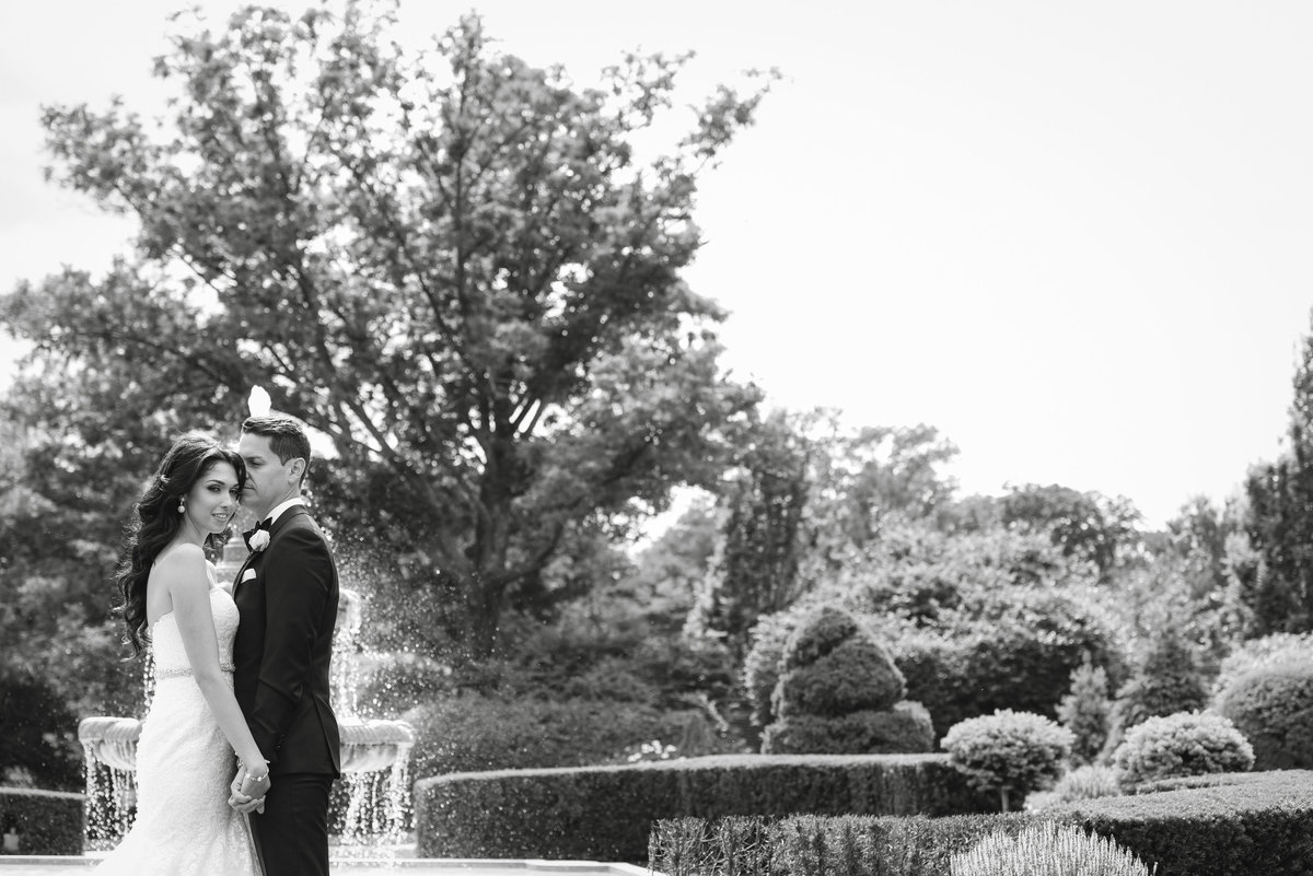 Black and white photo of bride and groom by the fountain of Glen Cove Mansion