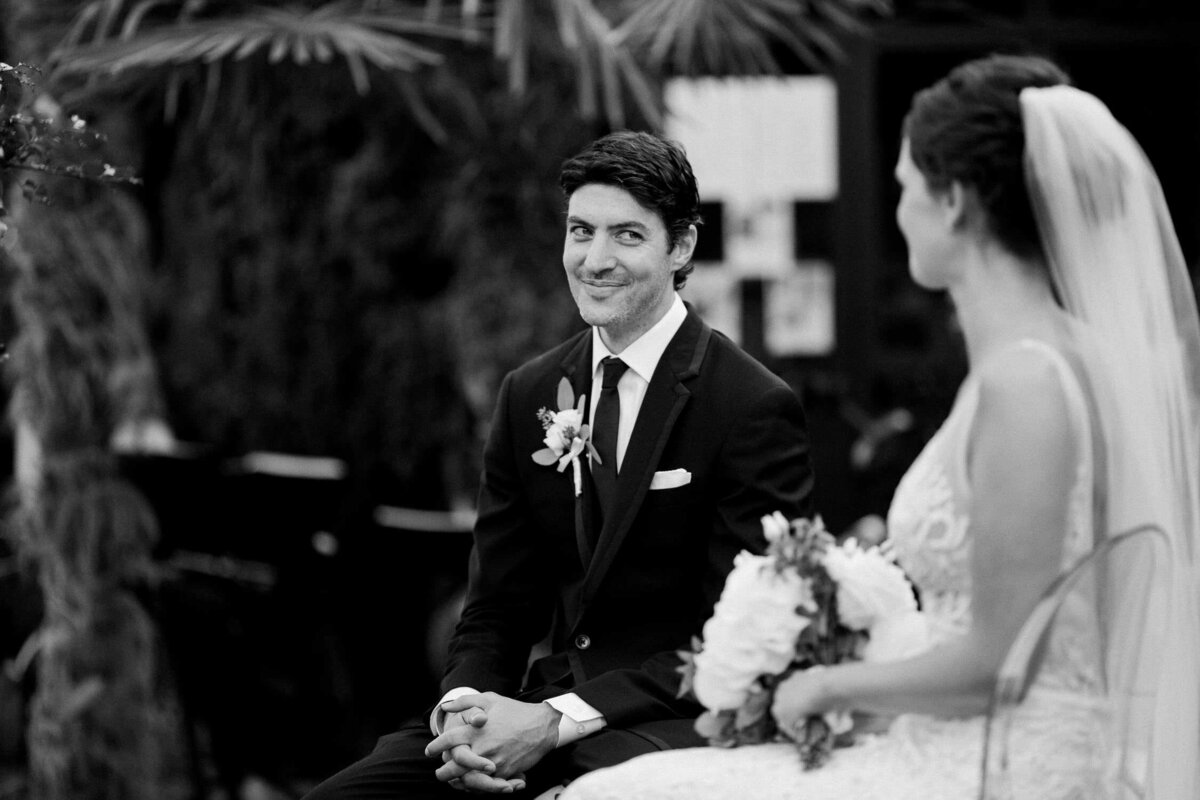 groom in tuxedo sitting at Italian wedding ceremony black and white