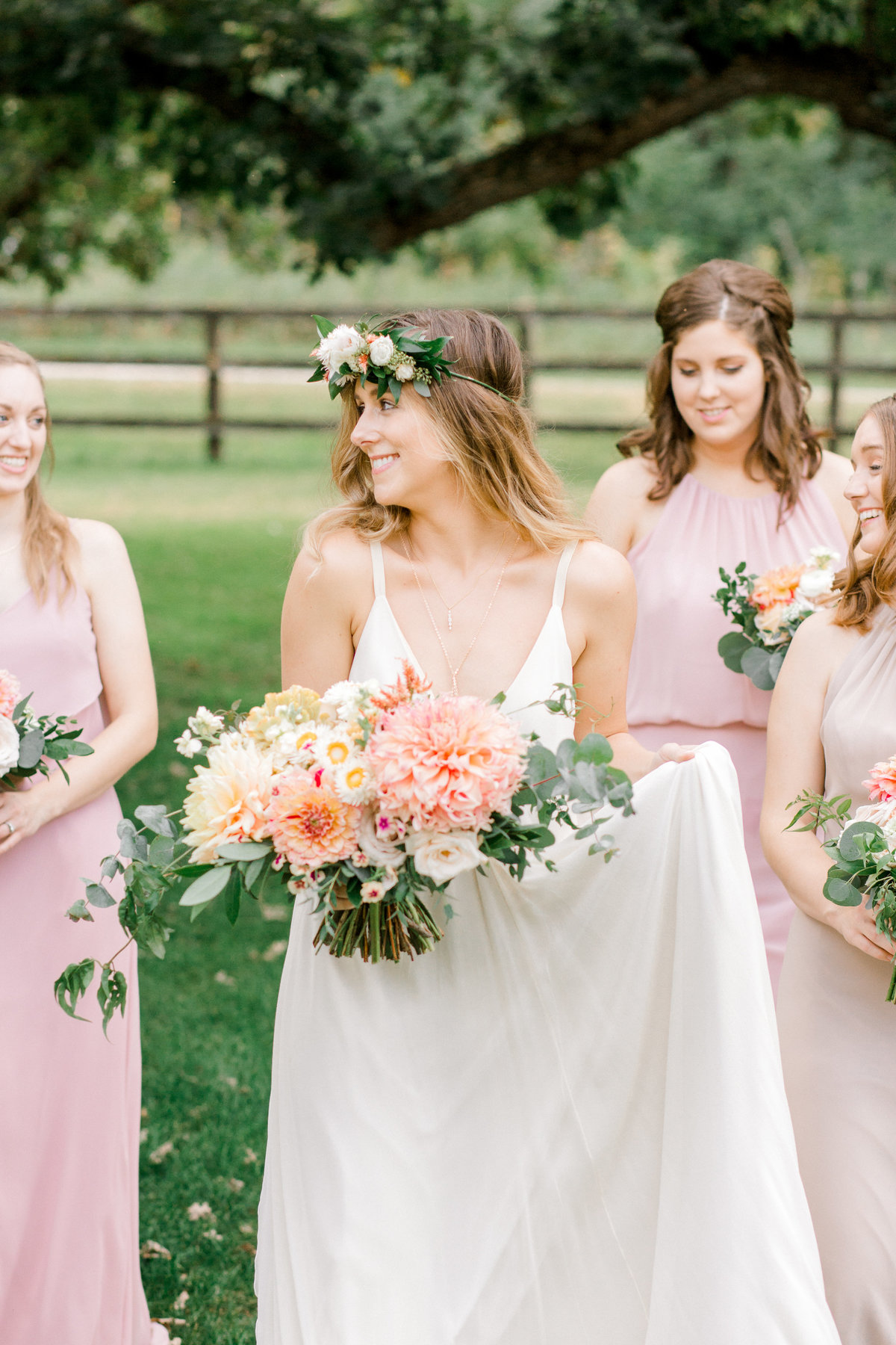 Bride walking with bridesmaids in carol hannah gown and fox and fern floral crown at mayowood stone barns