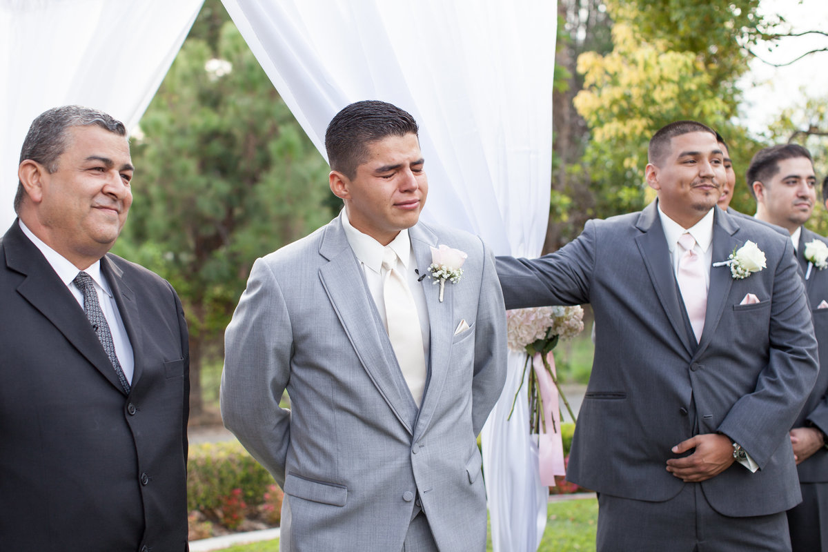 groom sees bride for the first time as she walks down the aisle at los angeles wedding