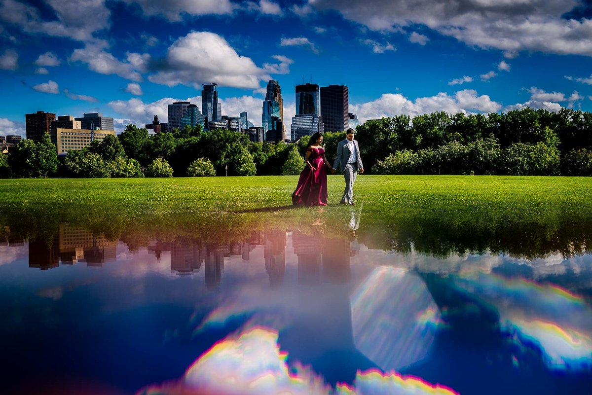 bride and groom walking in boom island park in front of Minneapolis skyline by stephane lemaire photography