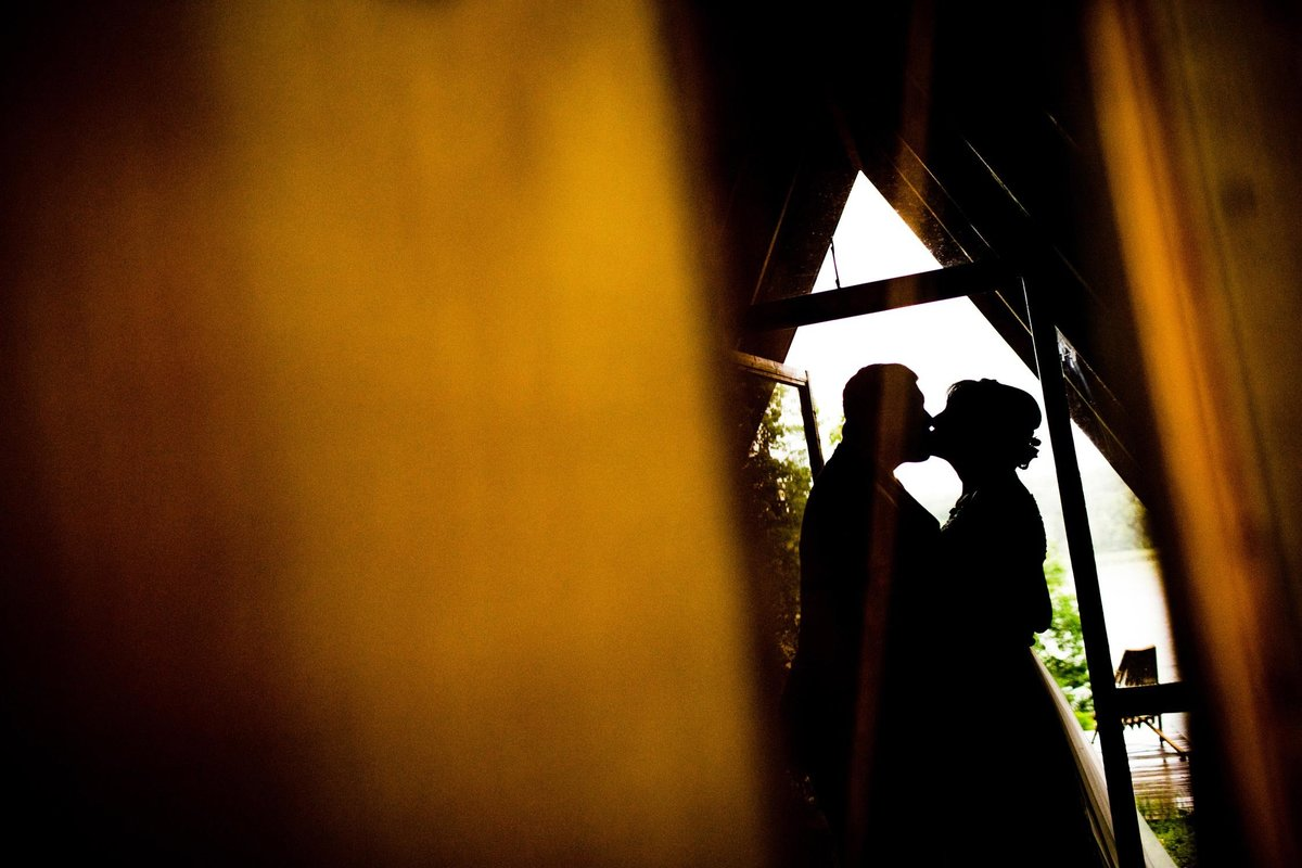 A couple kisses in silhouette during a Camp Wandawega wedding.