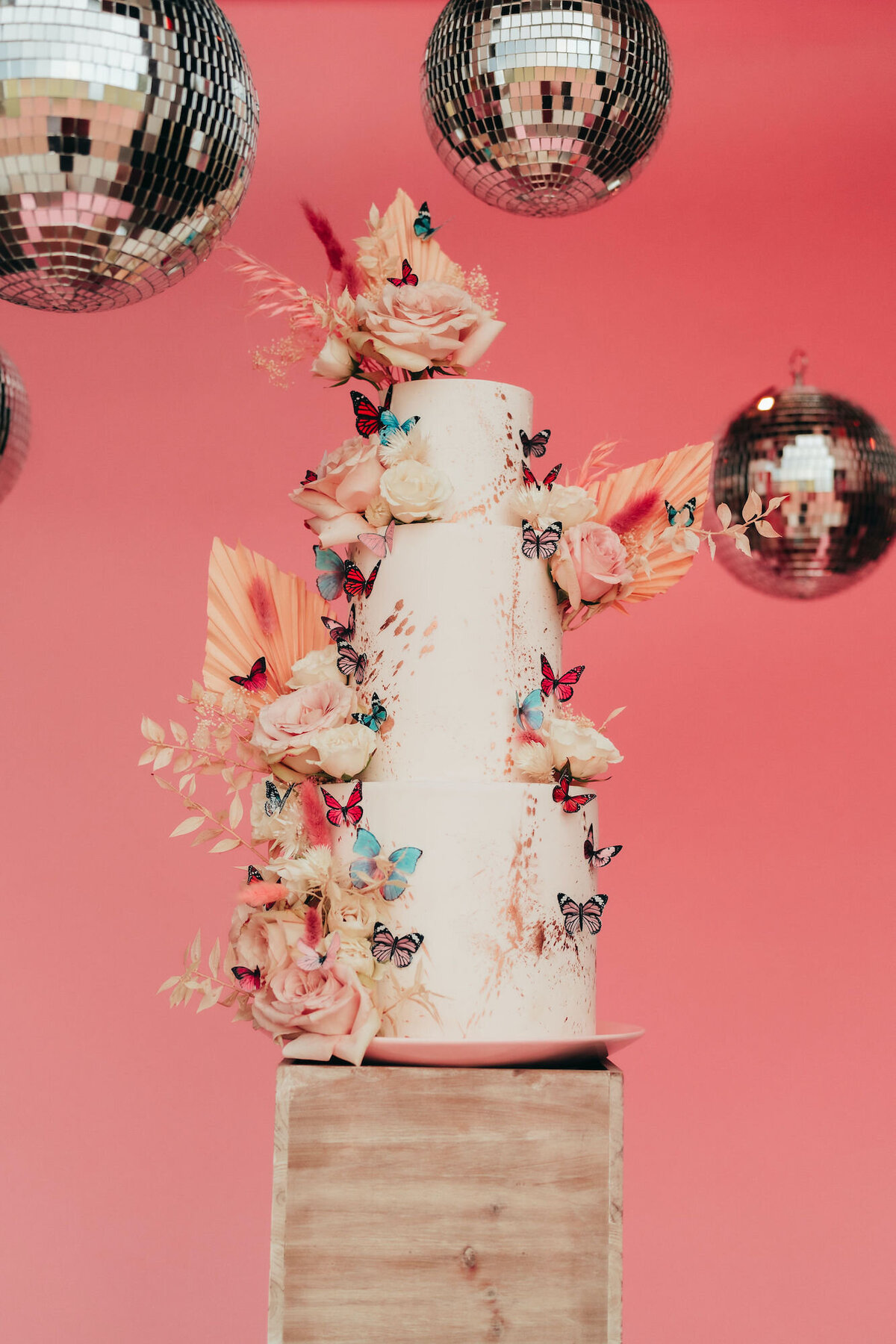 wedding cake decorated with florals and butterflies