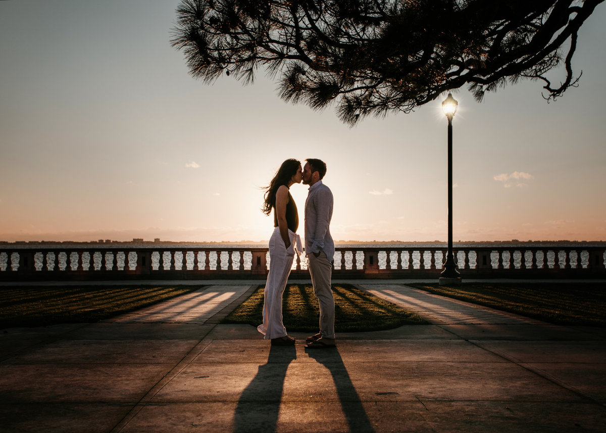 An image from a distance of an engaged couple standing and romantically kissing with an ornate railing behind them along a waterway with a city skyline, setting sun, and a glowing lamp post by Garry & Stacy Photography Co - Orlando engagement photographer