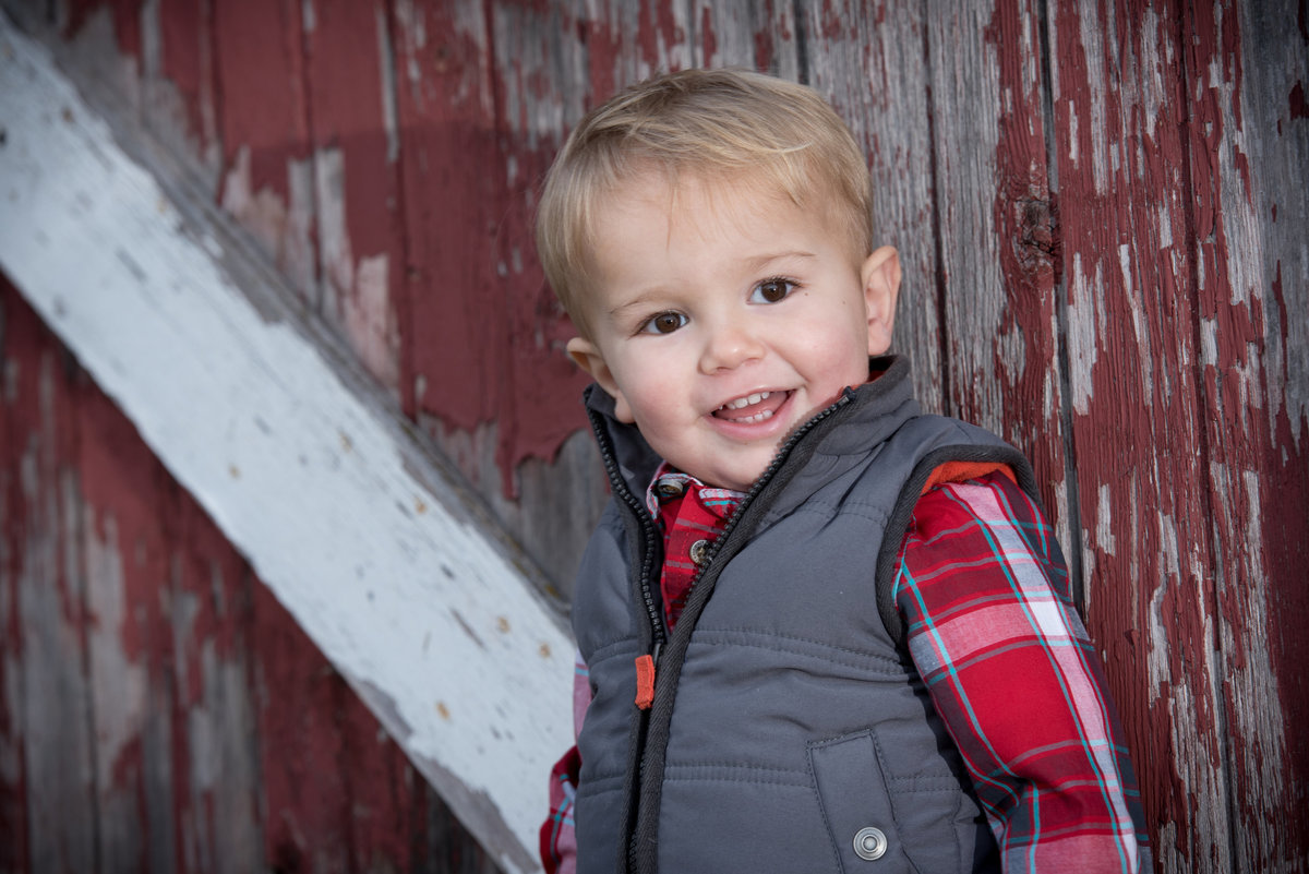 Smiling  toddler in a vest against a historic red barn during a family portrait
