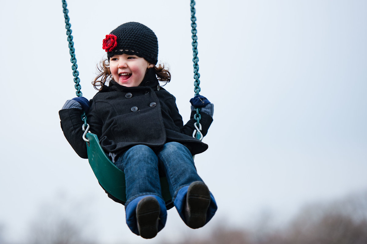 child on swing sticking tongue out