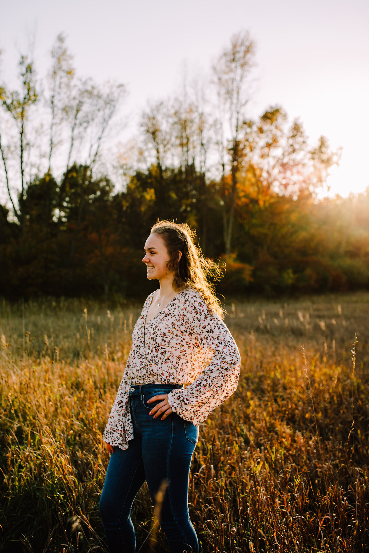 senior looking away from camera while standing in sunny field