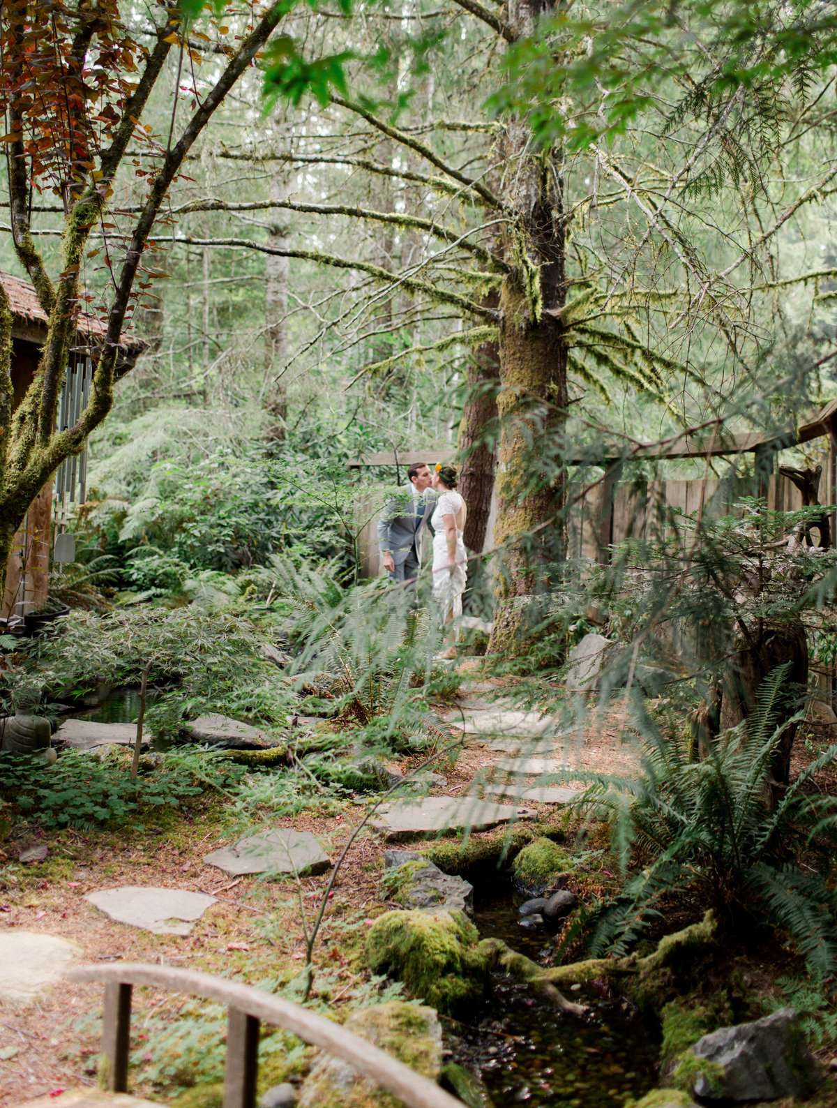 bride and groom see each other for first time among garden path in washington forest