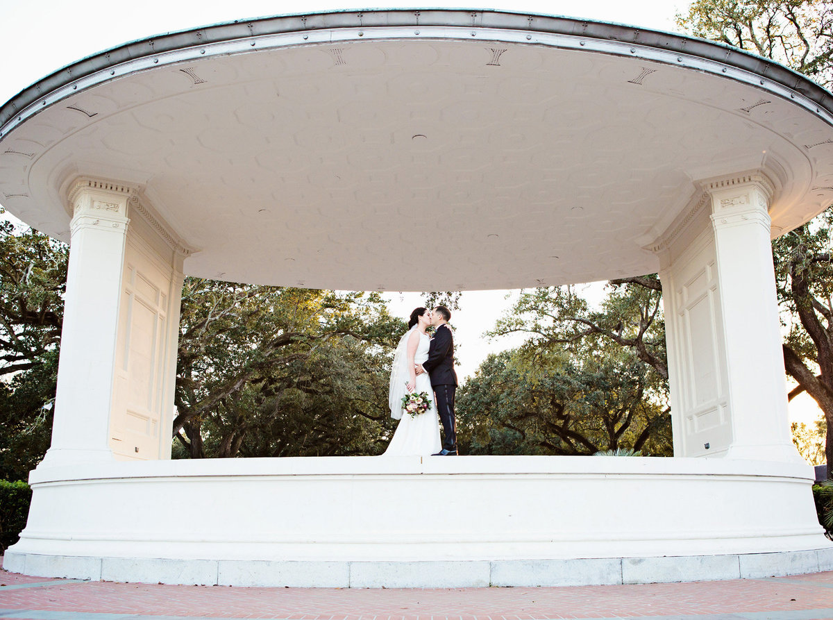 NOLA wedding couple kissing underneath the Newman Bandstand