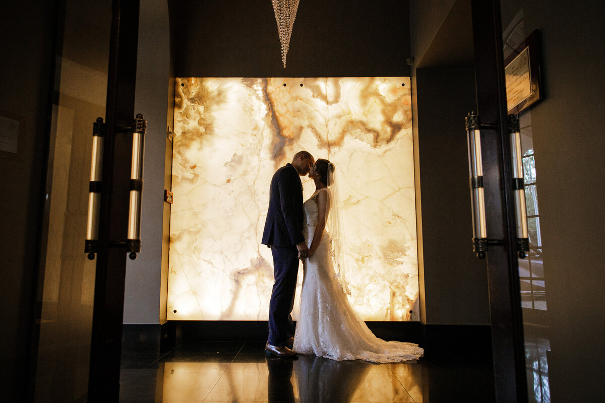 bride and groom pose in front of backlit marble wall at the coral gables country club in miami florida