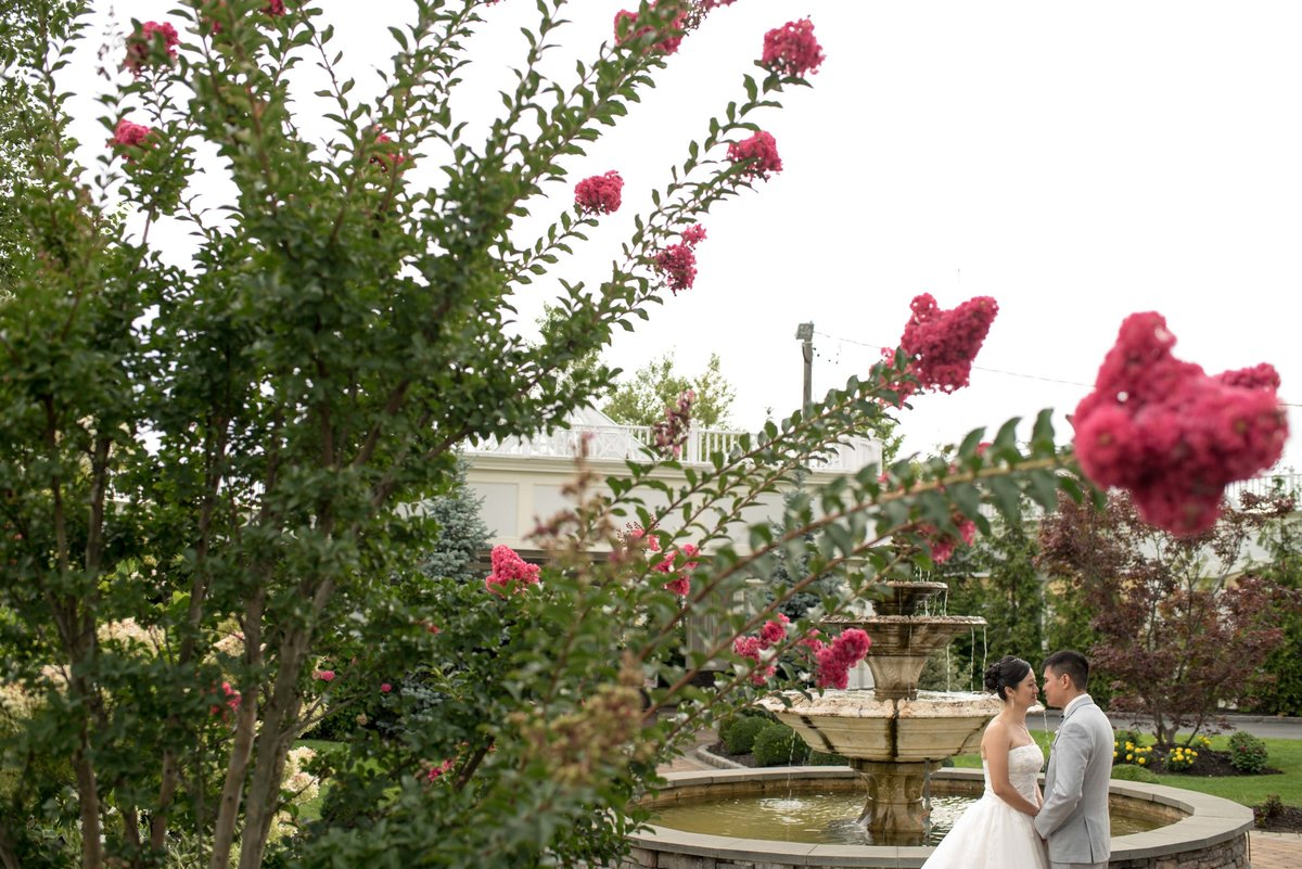 Bride and groom holding hands in front of the fountain at Bridgeview