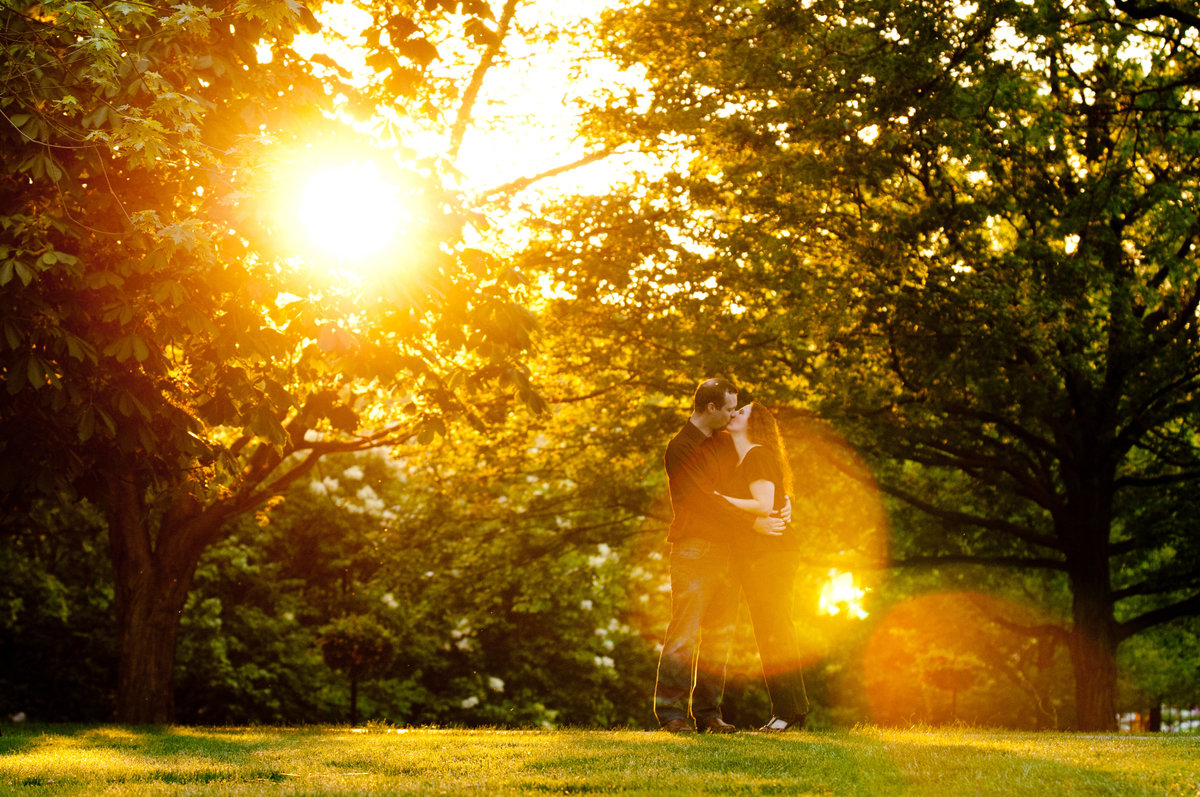 Kissing engagement couple enveloped in a sun flare