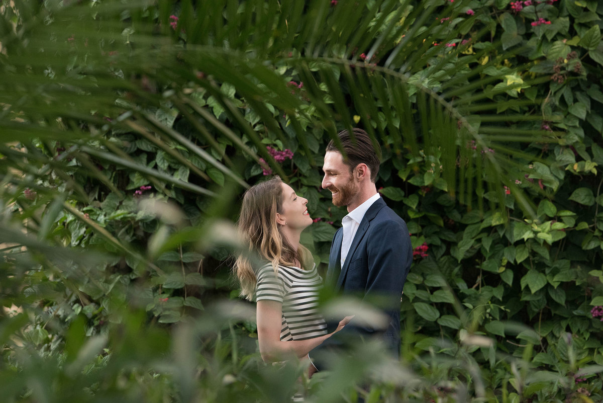 Engaged couple looking at each other in tropical surroundings.