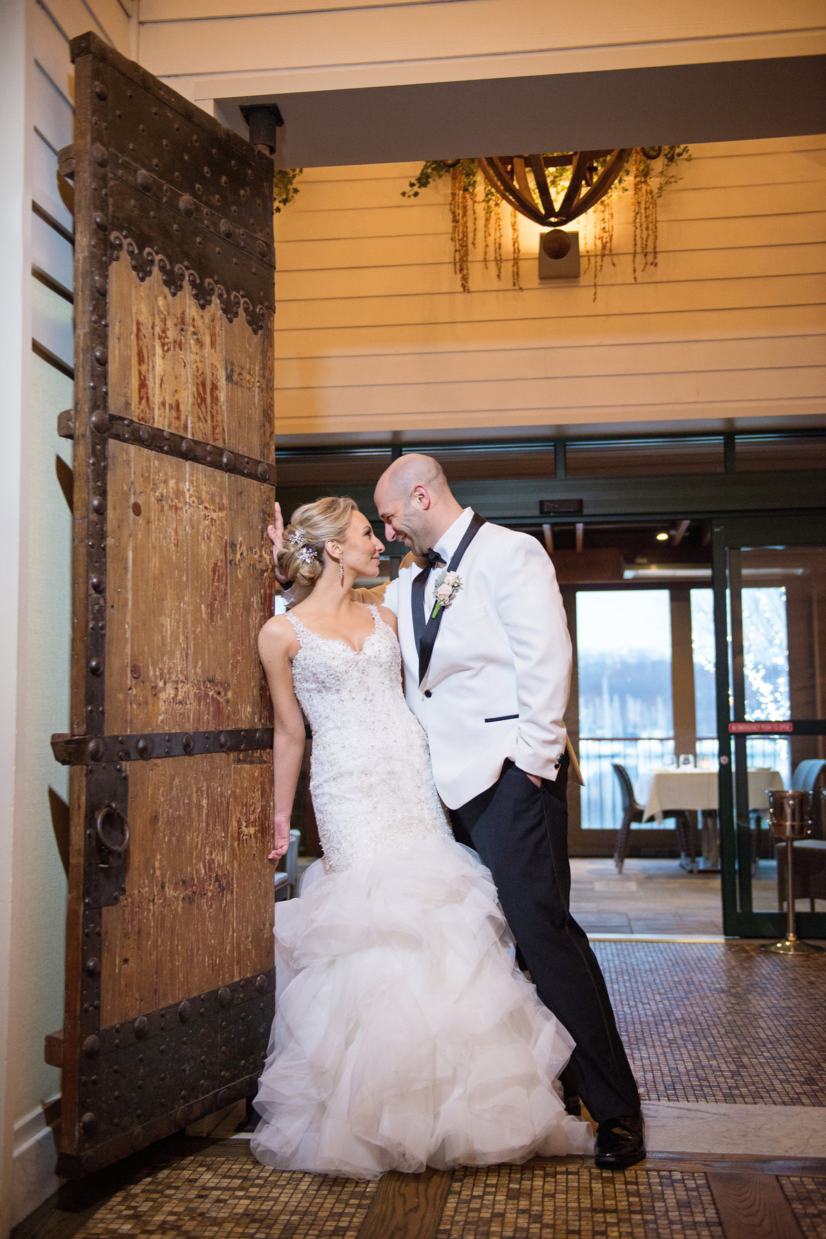 Bride and groom leaning on the door at Prime