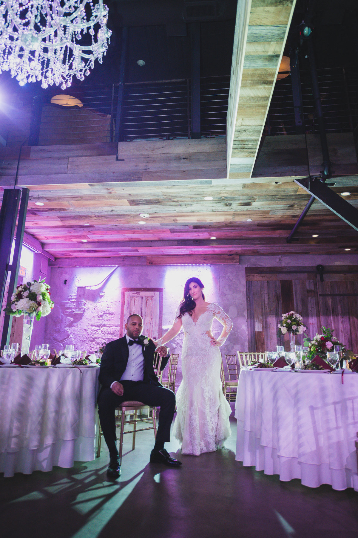 wedding photo of groom sitting with bride standing holding his shoulder in wedding reception at The Loft by Bridgeview