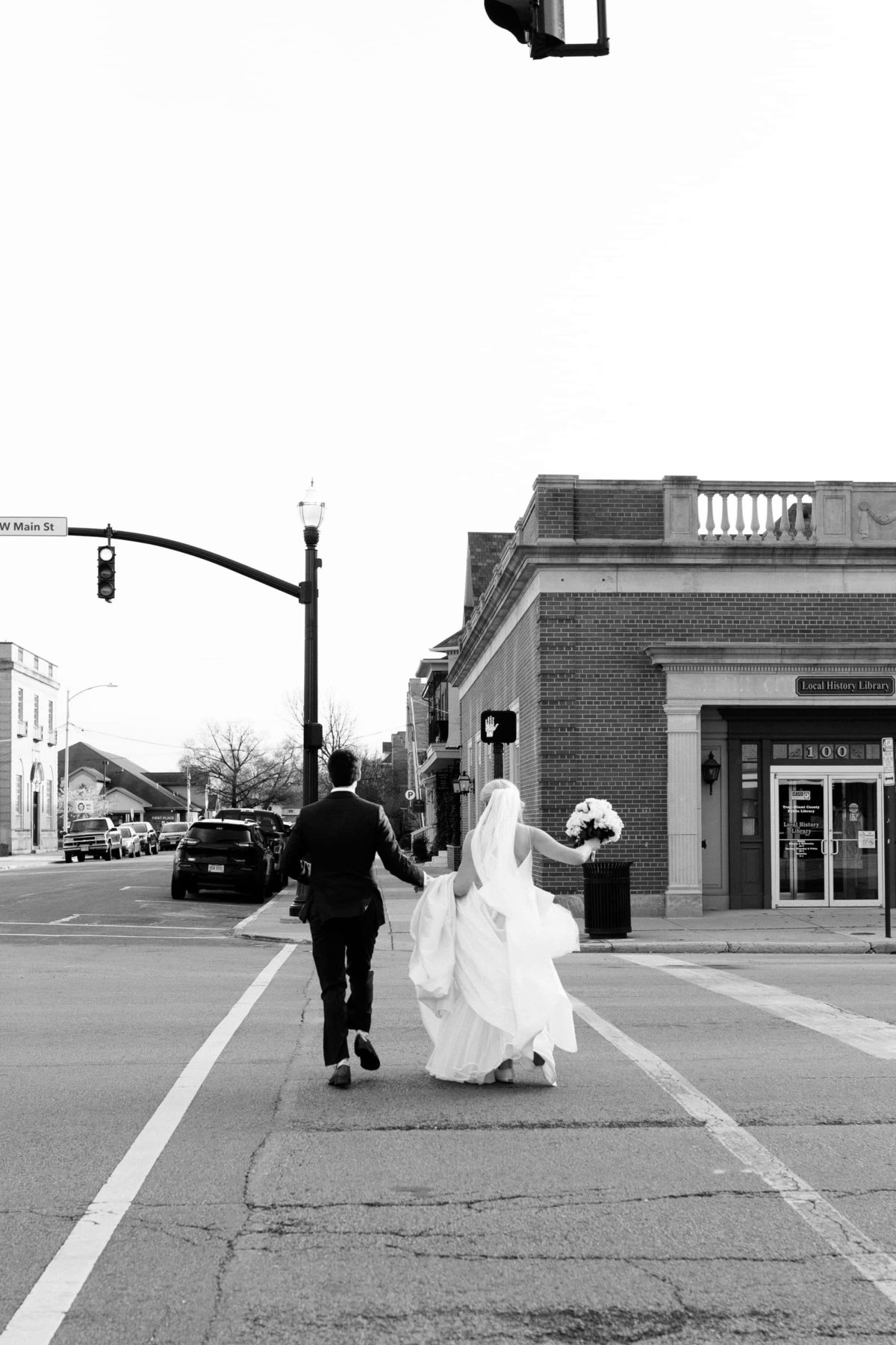 A bride and groom run across the street in the middle of a crosswalk