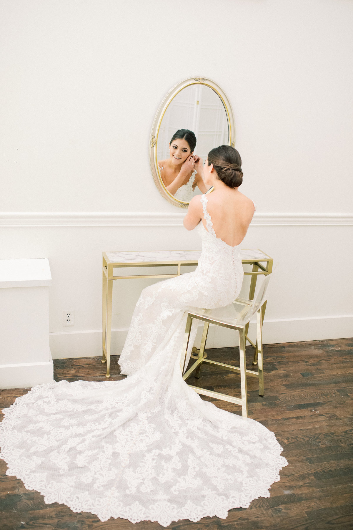 A bride puts on her earrings as she looks in a mirror by a vanity at the Transept in Over the Rhine Cincinnati, Ohio