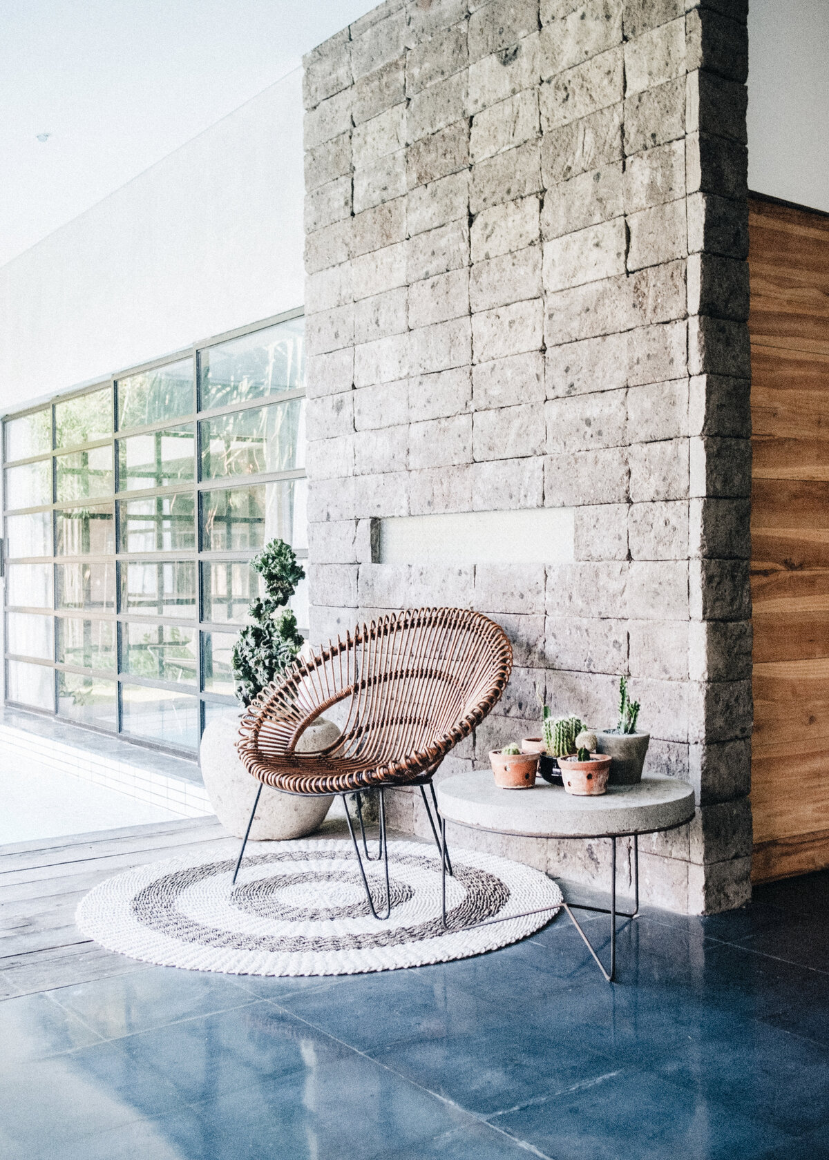 A rounded bohemian rattan is against an exterior stone wall, style with pots and a round rug.