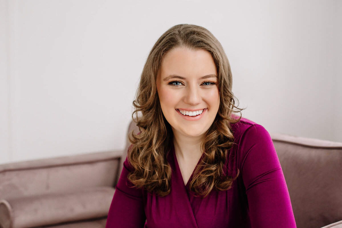 Business headshot of woman smiling on a sofa