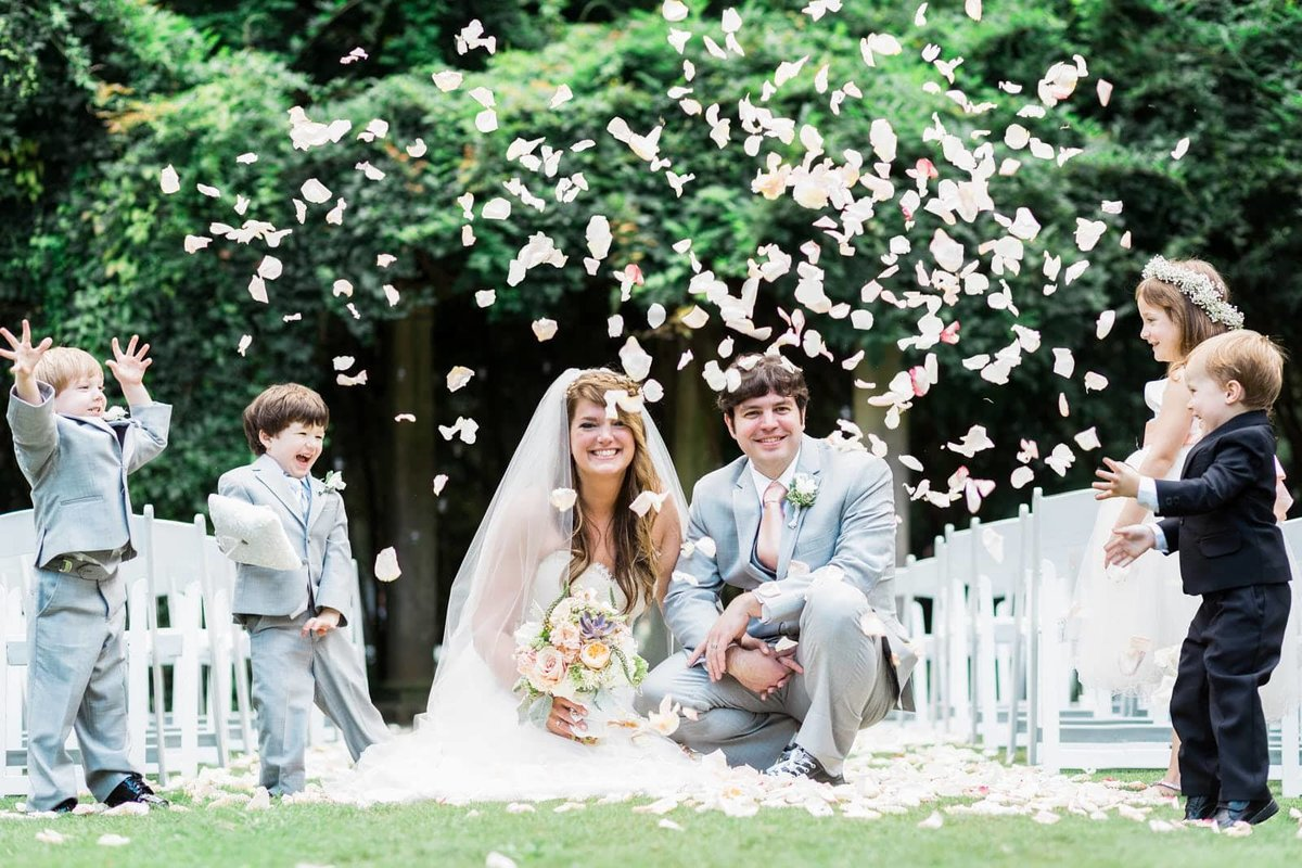 kids throw flowers over bride and groom Cator Wooldford Gardens