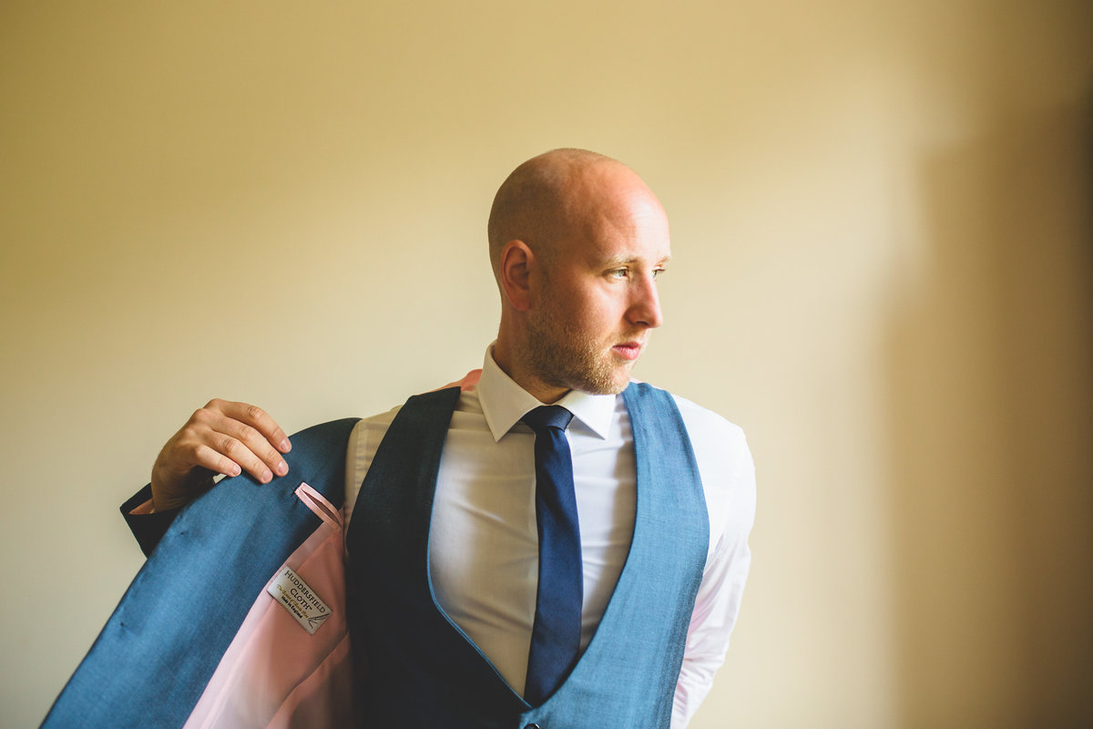 groom getting blue suit jacket on the morning of his wedding