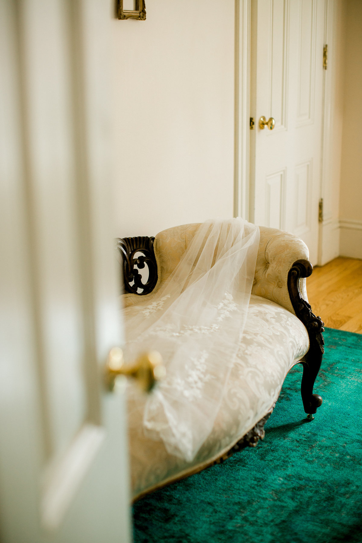 Veil laying on vintage sofa in bridal suite at Olympias Valley Estate in Petaluma California