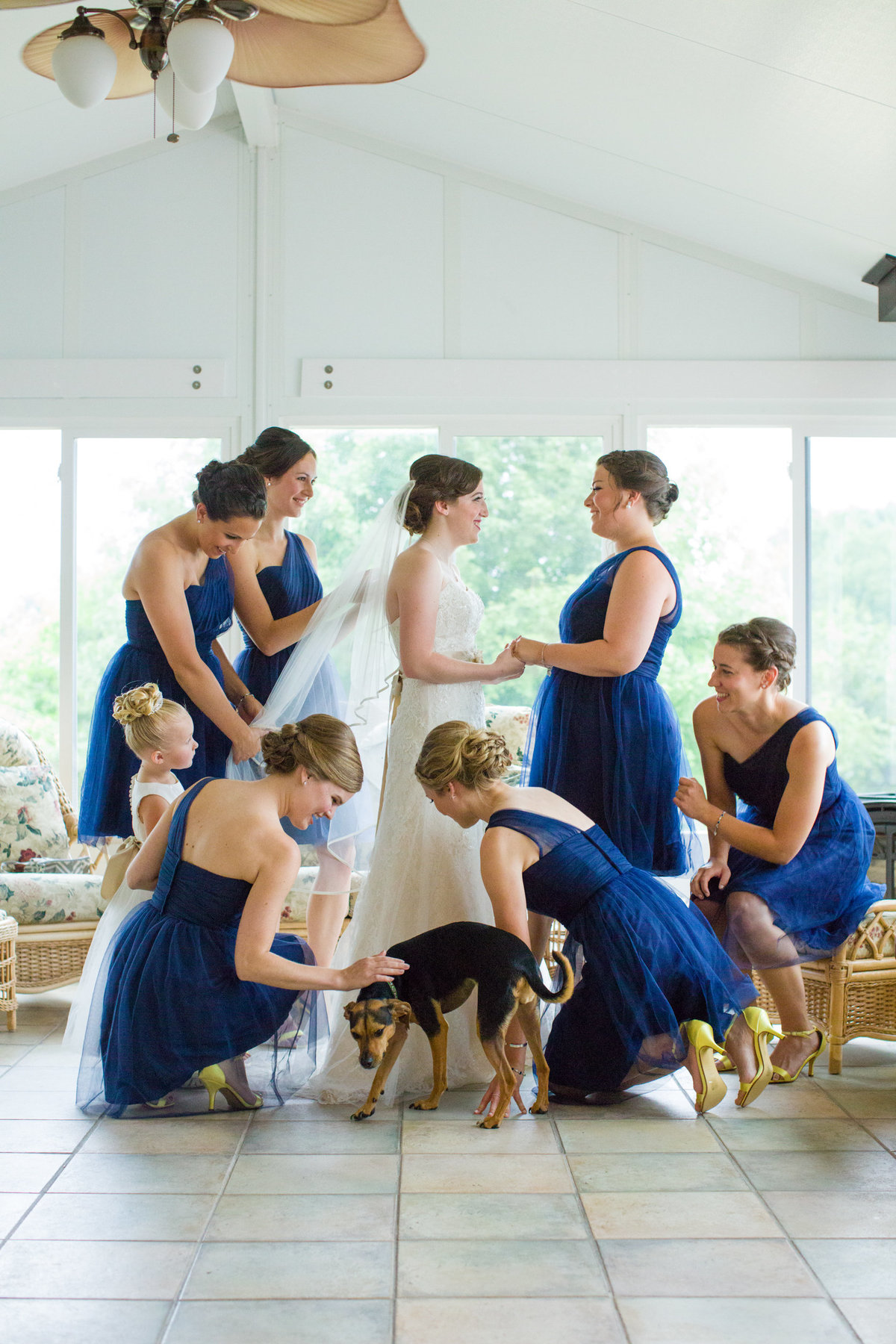 bridesmaids and bride with dog getting ready for wedding