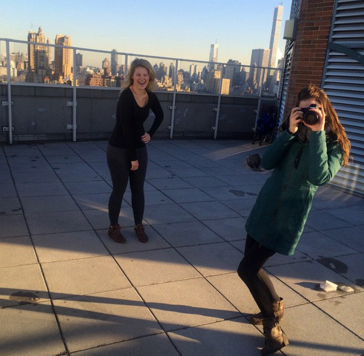Laura Volpacchio poses with camera as headshot client laughs while photographing on NYC rooftop.