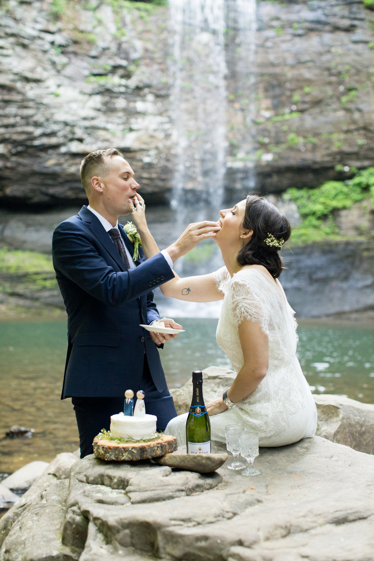 Cake cutting traditions by a waterfall by destination elopement photographer Rebecca Cerasani