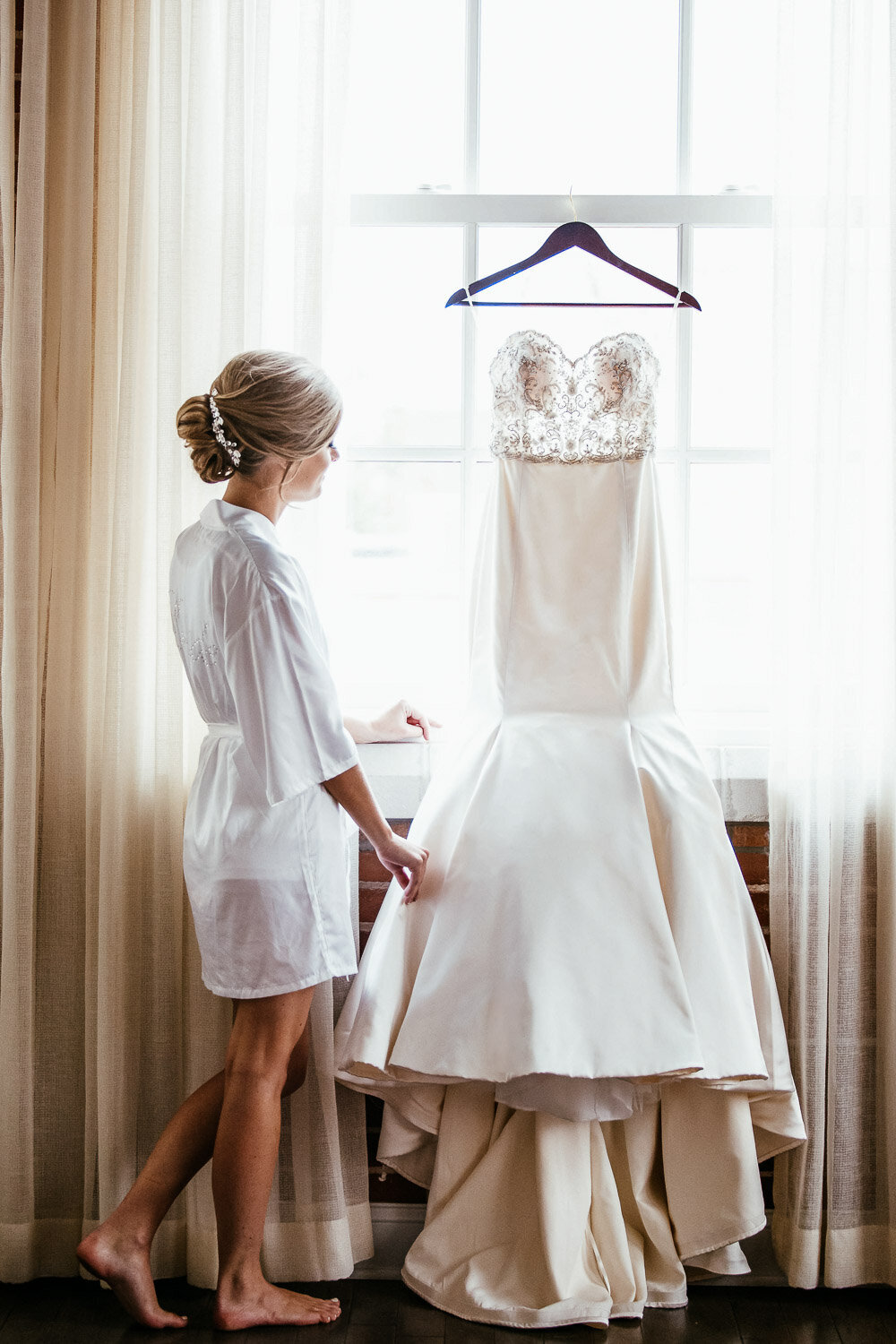 Bride looking at her hung up wedding dress