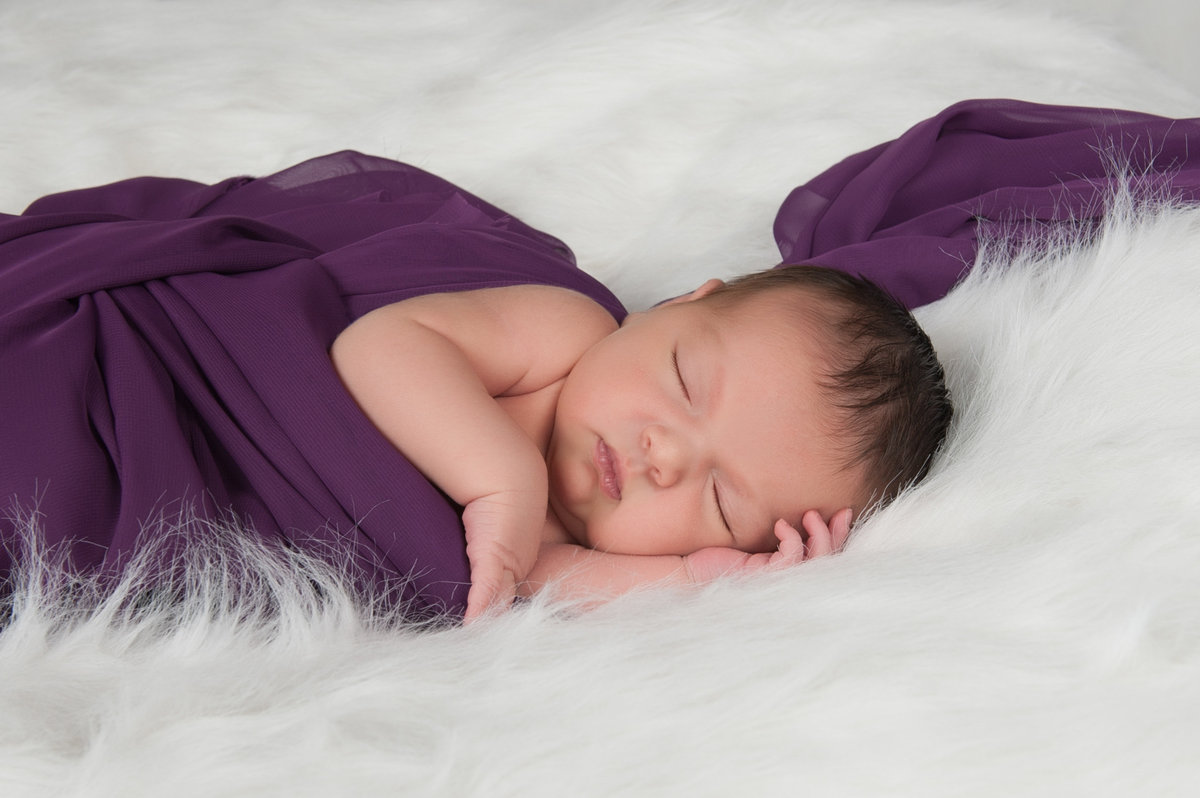newborn wrapped in purple on white fur