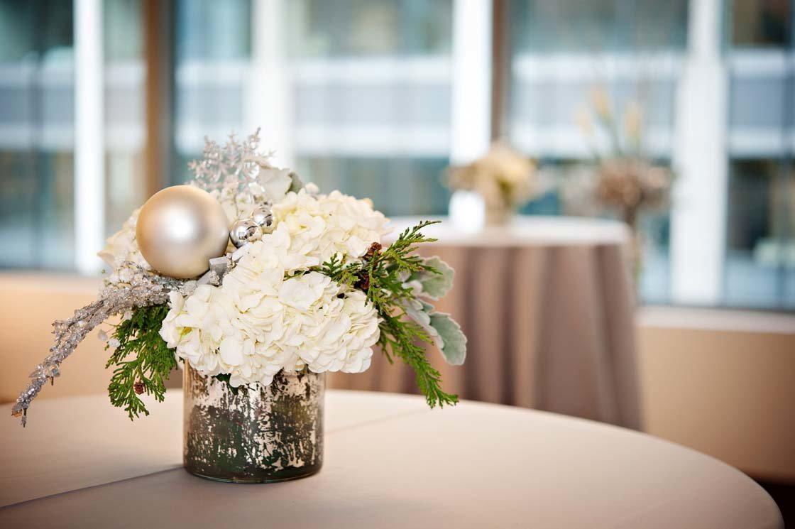 white winter holiday centerpiece with white hydrangea, evergreen, white ornaments in silver mercury vase