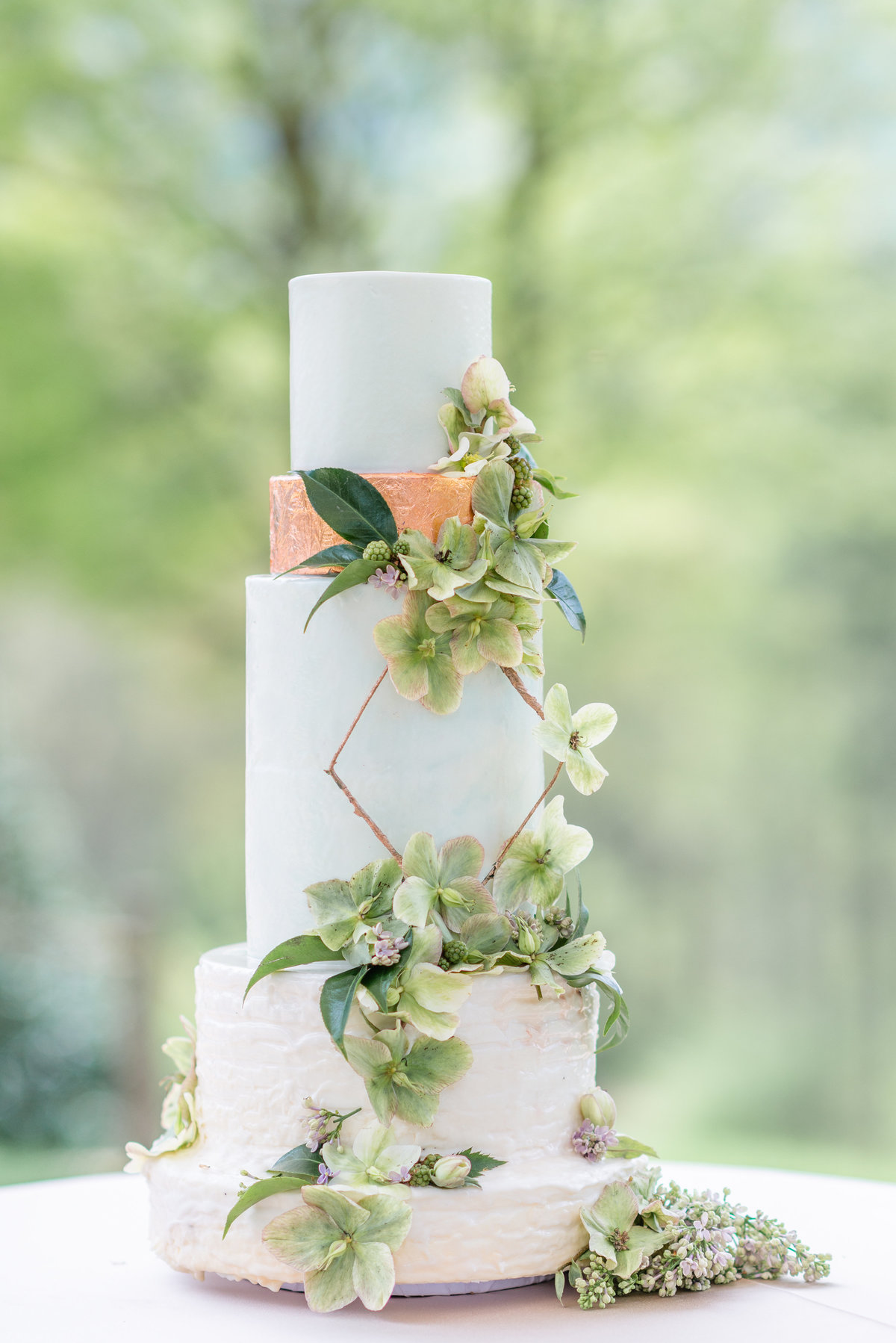 Wedding cake covered in greenery and copper