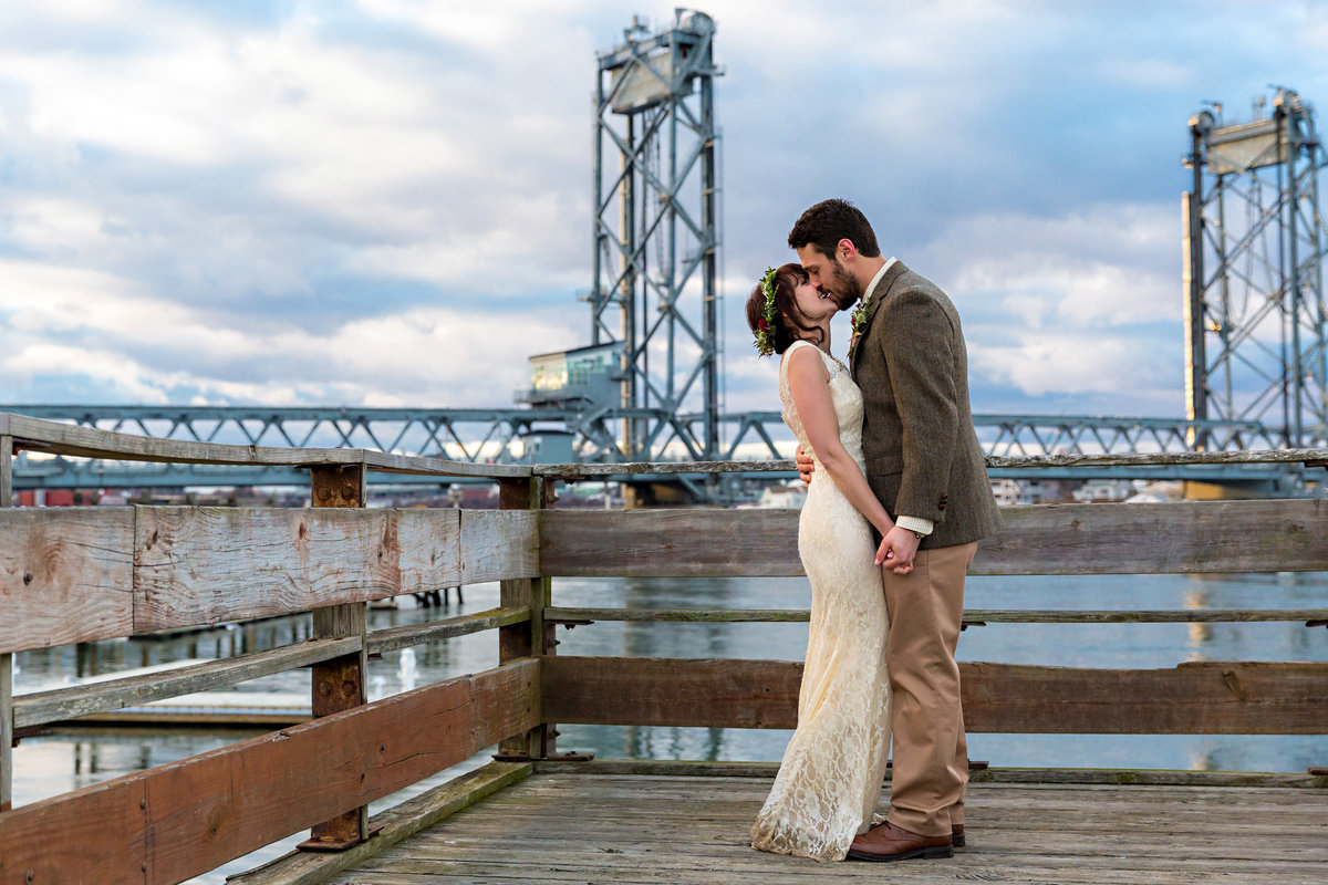 The newly eloped couple kiss in front of the Memorial Bridge in Portsmouth New Hampshire