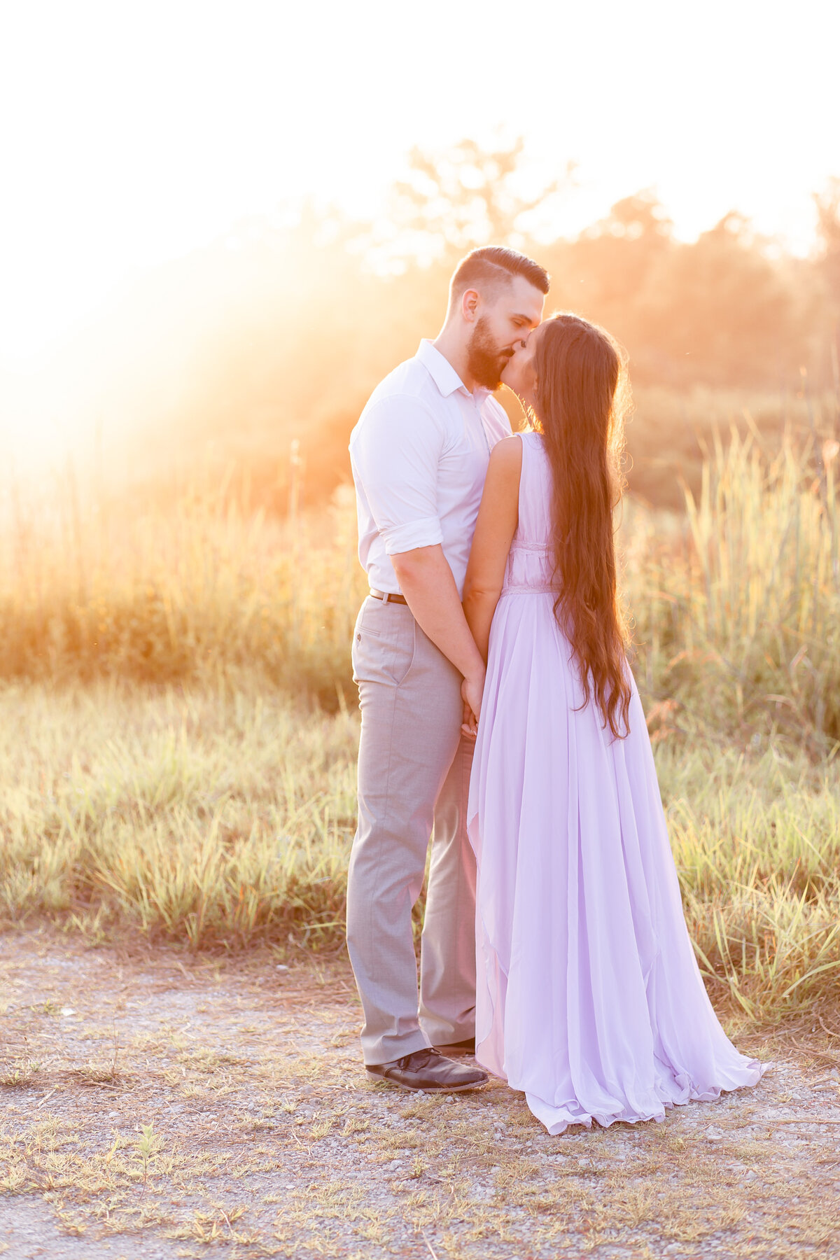 Summer Romantic Sunset Engagement Session guy kissing girl in lavender maxi dress in field on dirt road at Busch Wildlife in St. Louis by Amy Britton Photography Photographer in St. Louis