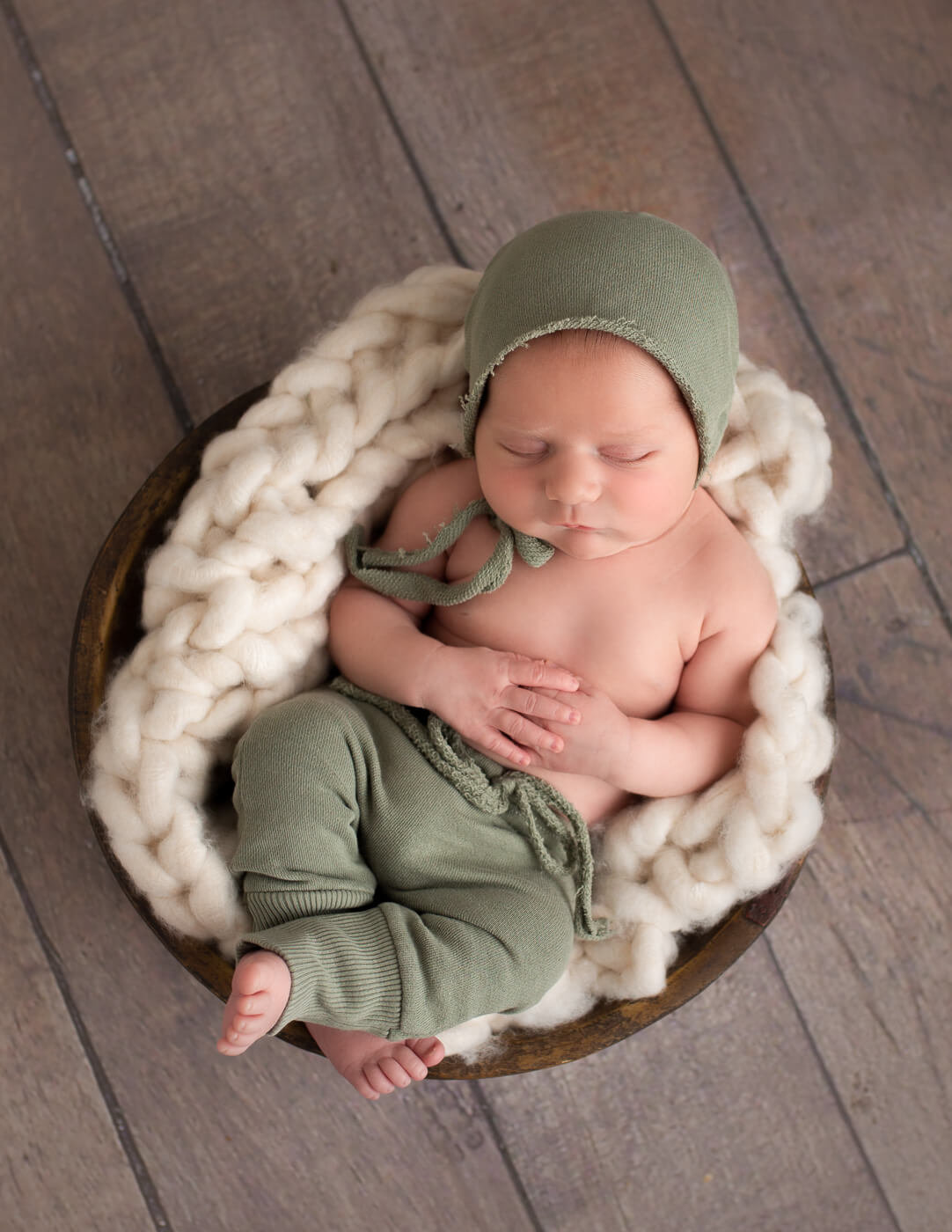 Sweet newborn boy posed in a wooden bowl in our in-home studio.