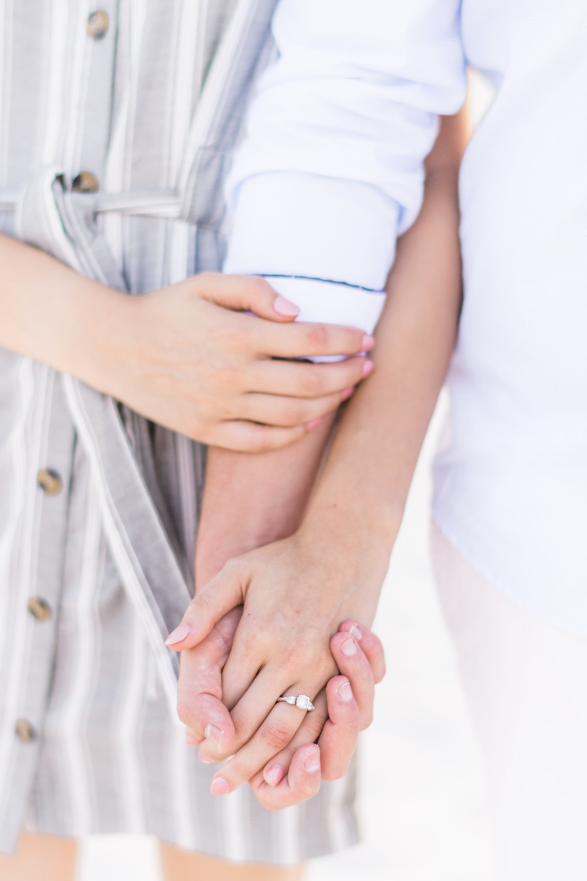 Up close of couple's hands with engagement ring