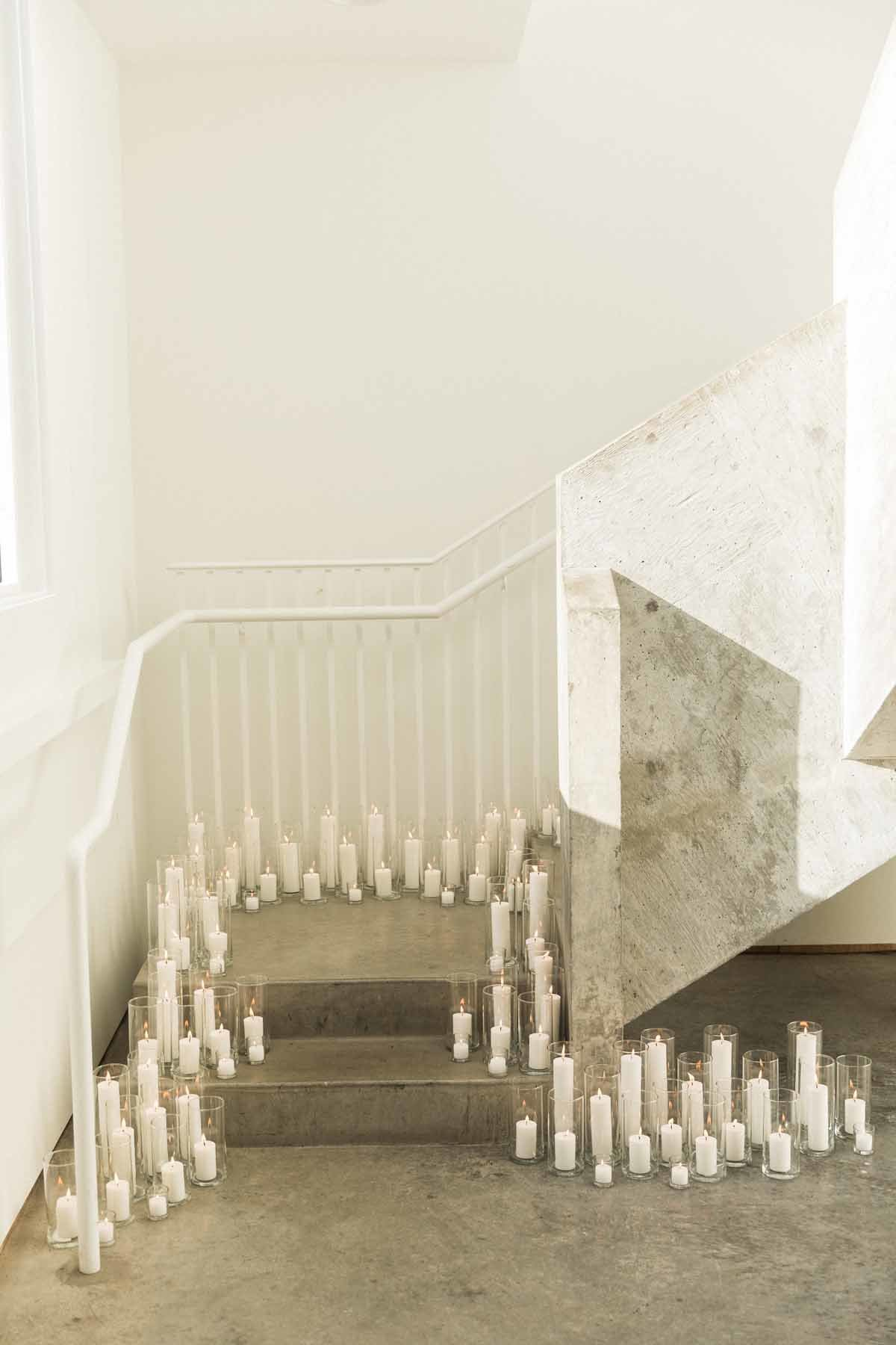 Candlelit stairwell at this simple and striking white wedding at Canvas Event space in Seattle