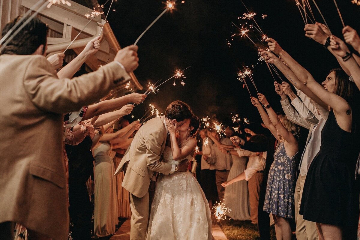Bride and groom kiss outside in dark surrounded by guests creating sparkler tunnel to send off couple
