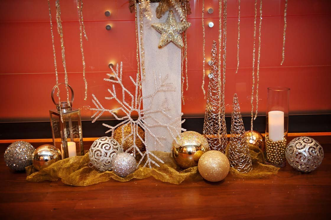 holiday decor with large gold ornaments, sparkle snowflakes, lanterns, and floorstanding white planter