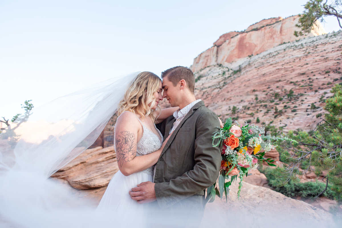 bride and groom touch foreheads as veil surrounds them at zion national park