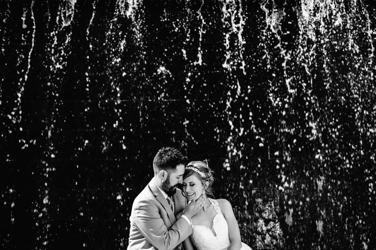 bride and groom wedding portrait in front of water wall