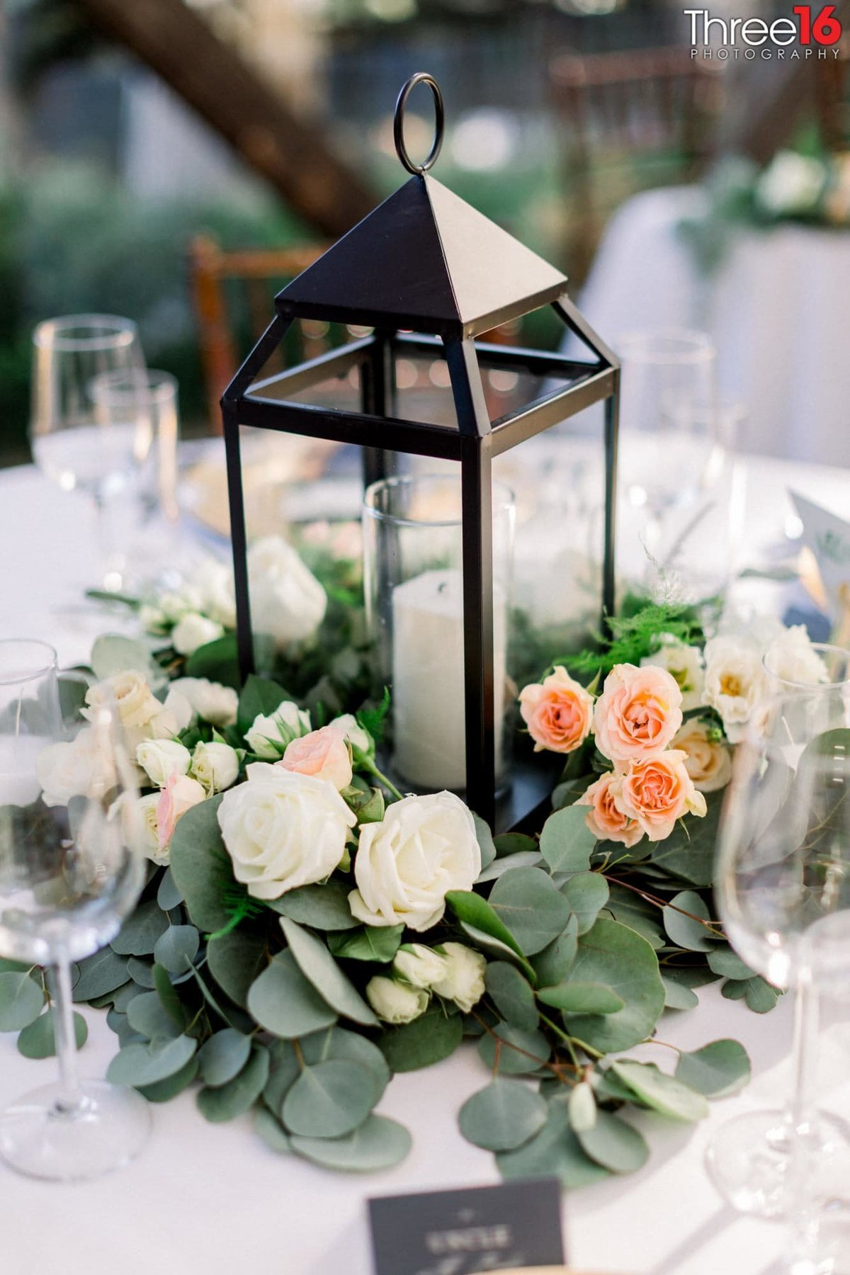 Centerpiece at a wedding reception that includes a candle surrounded by flowers