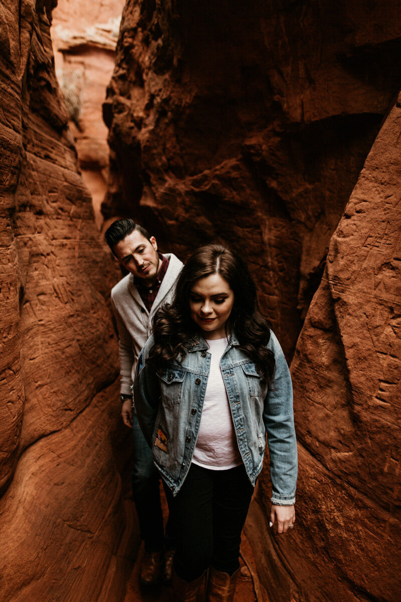 woman leading man through red rock canyon