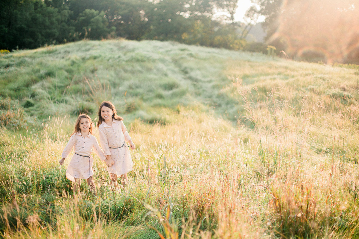 two sisters play in golden summer fields minnesota