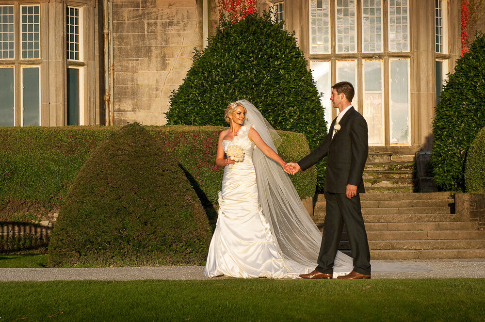 Bride in satin mermaid wedding dress and long veil, holding white flower bouquet, holding hands with groom wearing a black wedding suit at Muckross House